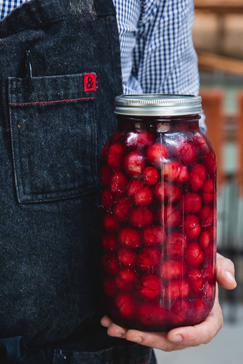 Holding a jar of pickled cherries